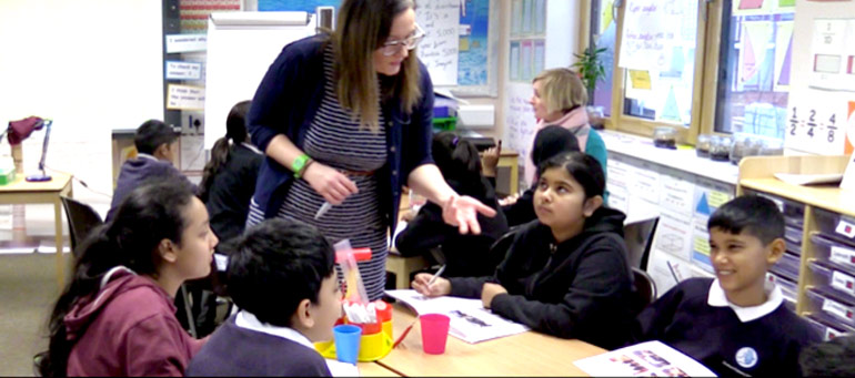 A teacher talks to a table of children listening