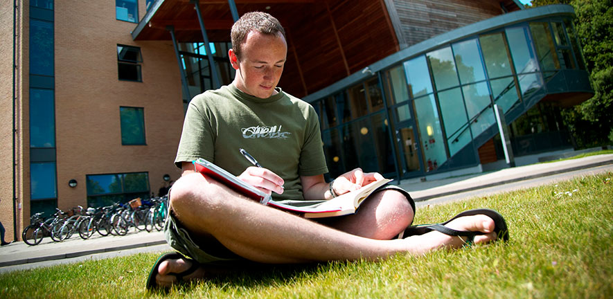 Student reading sits on grass outside of Faculty of Education
