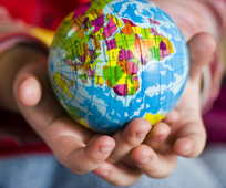 childs hands holding a globe
