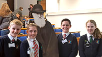 Four pupils from Buckden Primary school with a cardboard cut out of Charles Darwin