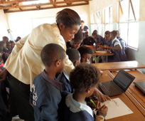 A teacher and pupils in an African school looking at a laptop computer