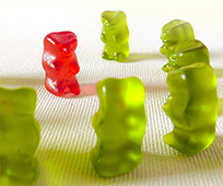 green jelly teddies stand around a red jelly teddy