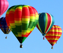 Hot air balloons rise in to blue sky