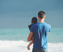 A father and child look out to a blue sea