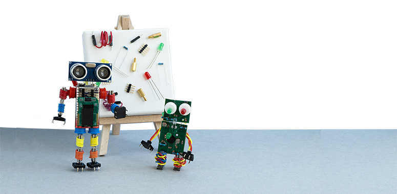 Adult and child robots made from loose parts stand in front of a white board