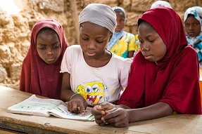 Girls in classroom looking at a book Niger
