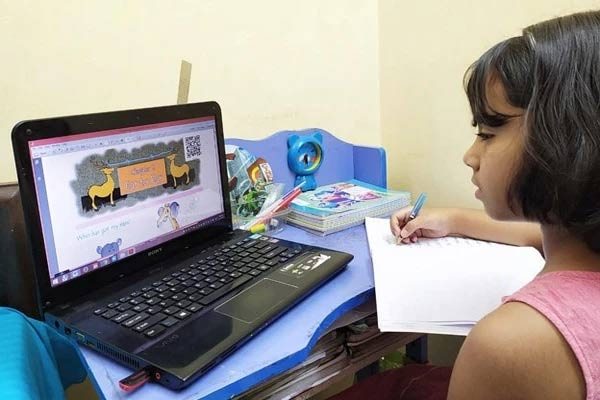 A child in India working at a laptop computer