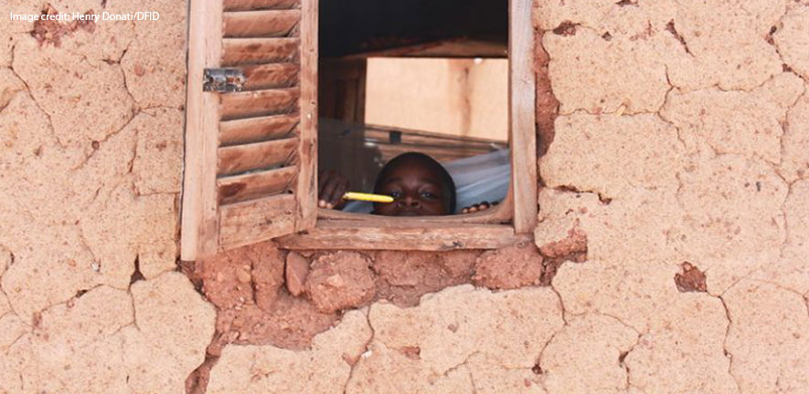 A child in Africa peeks out of the window of a house