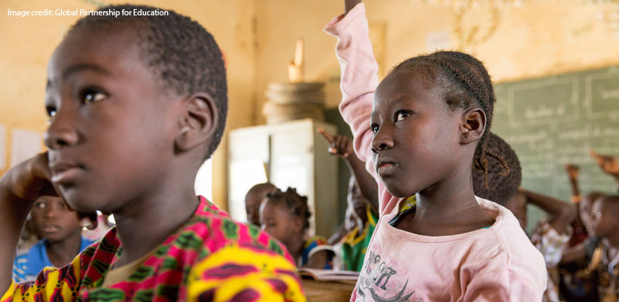 Children in a classroom in Africa looking attentive, a girl pupil has her hand raised