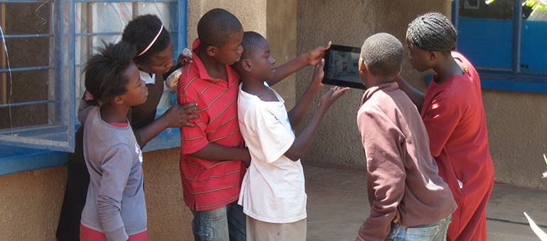 group of happy looking girls and boys stand looking at a digital tablet