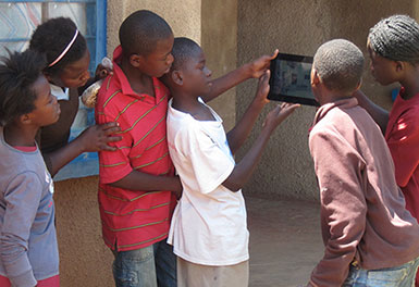 a group of girls and boys standing and looking at a digital tablet