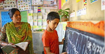 Teacher and student in classroom at board