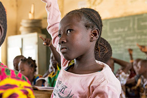An african girl in class with hand in the air
