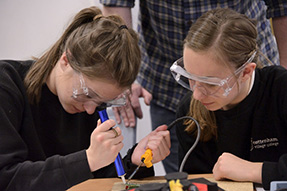 Two secondary school girls with protective glasses are soldering