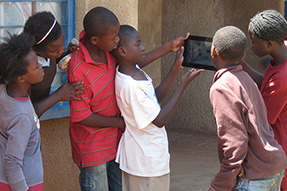 School children stand looking at something on a tablet computer