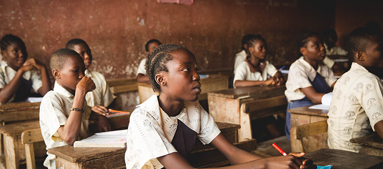African girls sit at desks in a school classroom